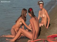 Three naked sisters playing with sand on the beach