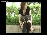 Bizarre public movie features a teen whore stuffing objects in her hole in while sitting outdoors