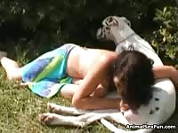 Cute young teen enjoying her dog's cock while out in the sun
